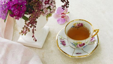 A porcelain cup of the tea with a white vase with flowers and a pink shawl. Still life.