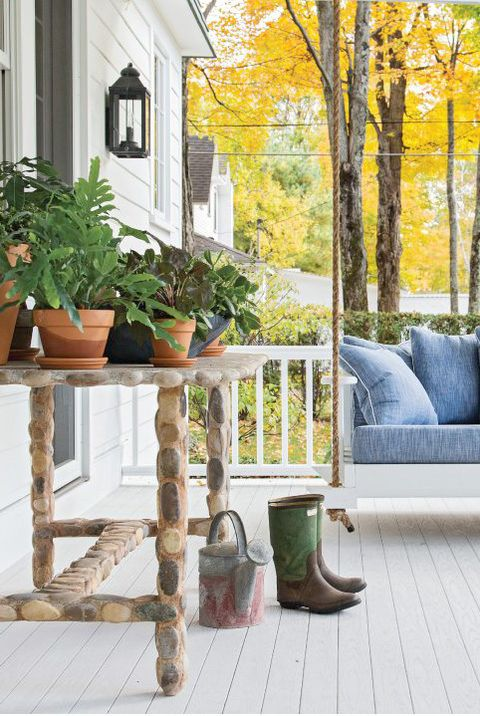 white porch with swing bench and pots
