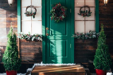 porch with wooden doors and a threshold with christmas decor