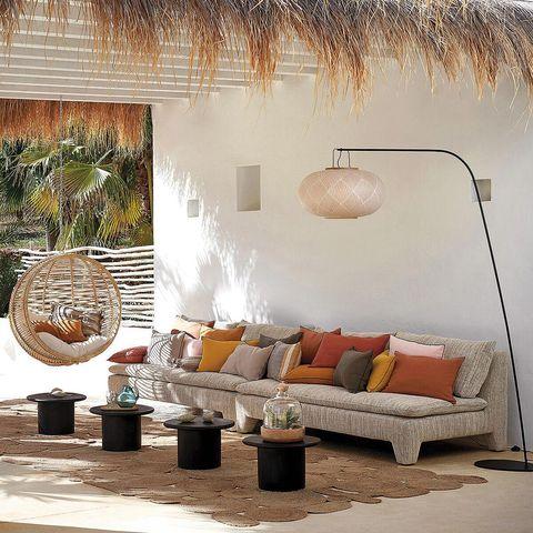 porche con sofá y butaca colgante lámpara de pie