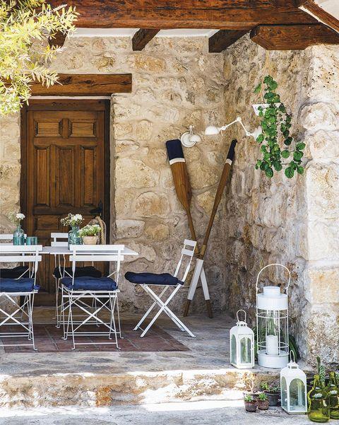 comedor exterior blanco de metal de casa de piedra
