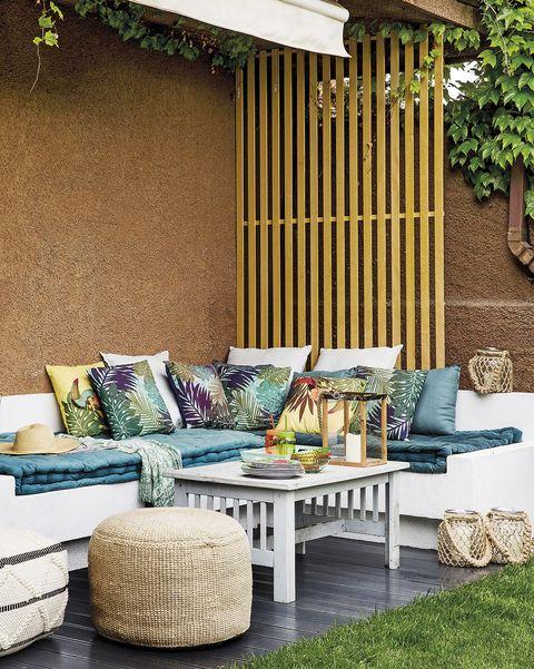 porche con sofá en esquina blanco y cojines tropicales