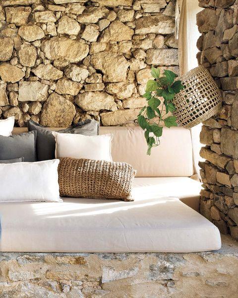 porche con paredes de piedra y colchones para la siesta