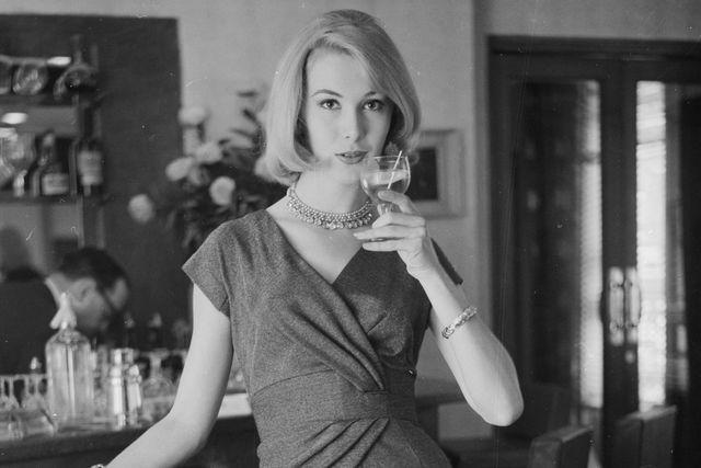 mujer elegante se bebe una copa de chardonnay 1960