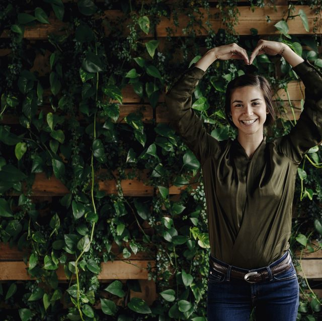 Portait of smiling young woman shaping heart at wall with climbing plants