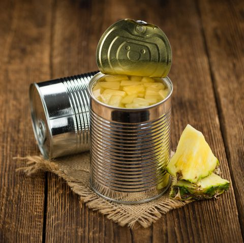 portion of chopped pineapple preserved on wooden background, selective focus