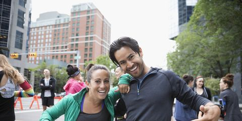 Portrait enthusiastic couple pointing to marathon bibs on urban street