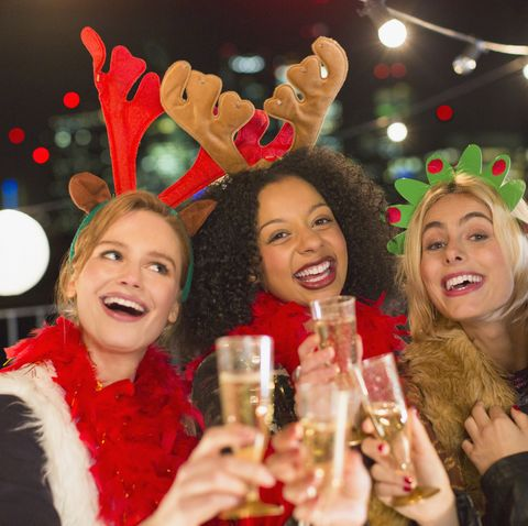 Portrait enthusiastic young women wearing Christmas reindeer antlers and drinking champagne at party