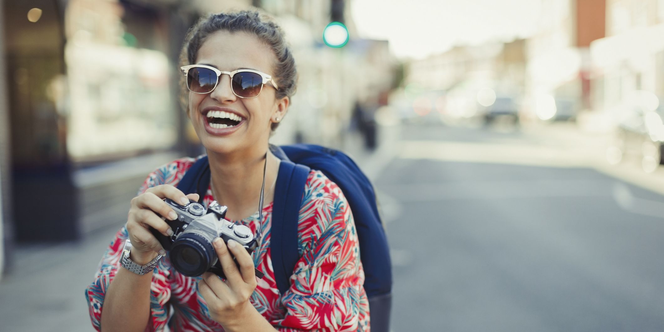 Portrait laughing, enthusiastic young female tourist in sunglasses photographing with camera on urban street