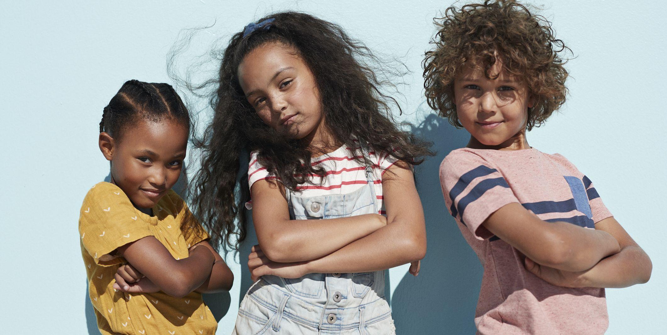 Portrait of 3 cool kids together on blue backdrop in summer