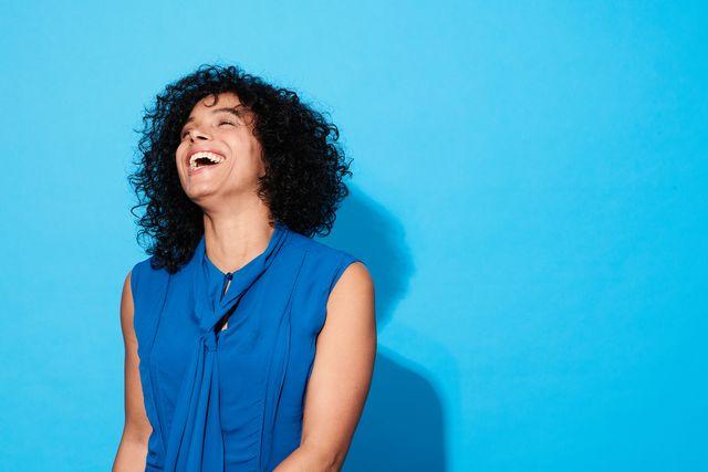 una ragazza ride su sfondo azzurro