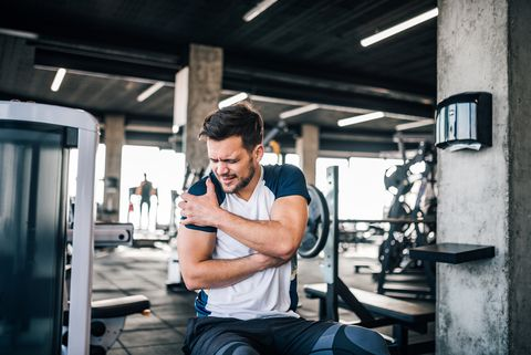 Portrait of a handsome man with strong facial expresion and injured arm while exercising in the gym.