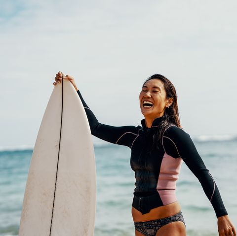 Portrait of a mature female athlete with her surfboard with a confident expression