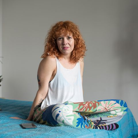 Portrait of a red-haired woman sitting on her bed