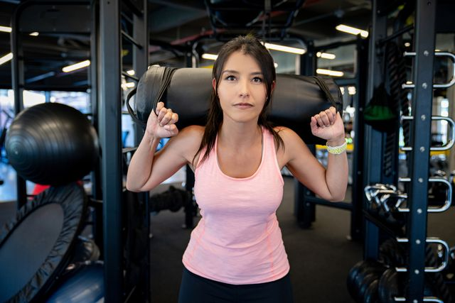 portrait of a woman working out at the gym doing squats with a sand bag