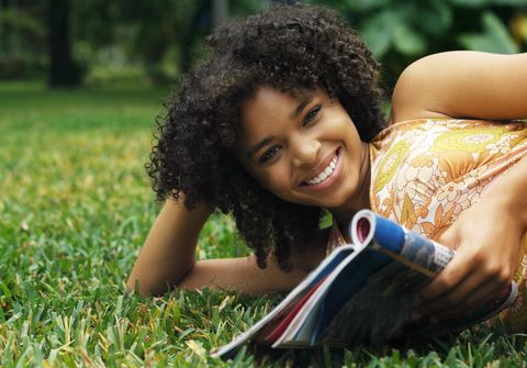 portrait of a young girl lying on a lawn reading a magazine