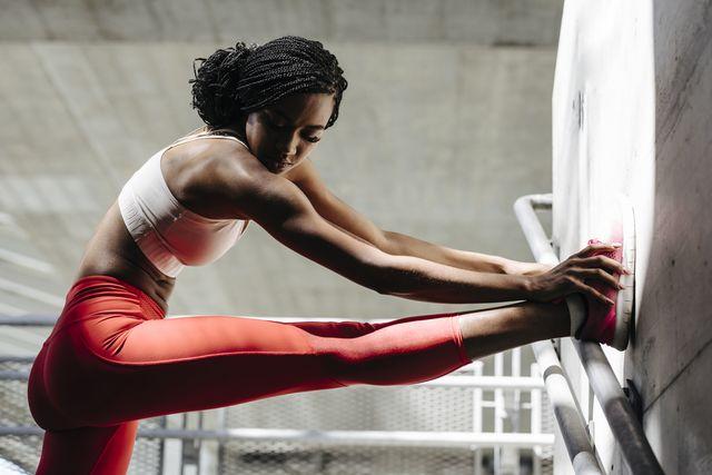 portrait of african sportswoman stretching her leg