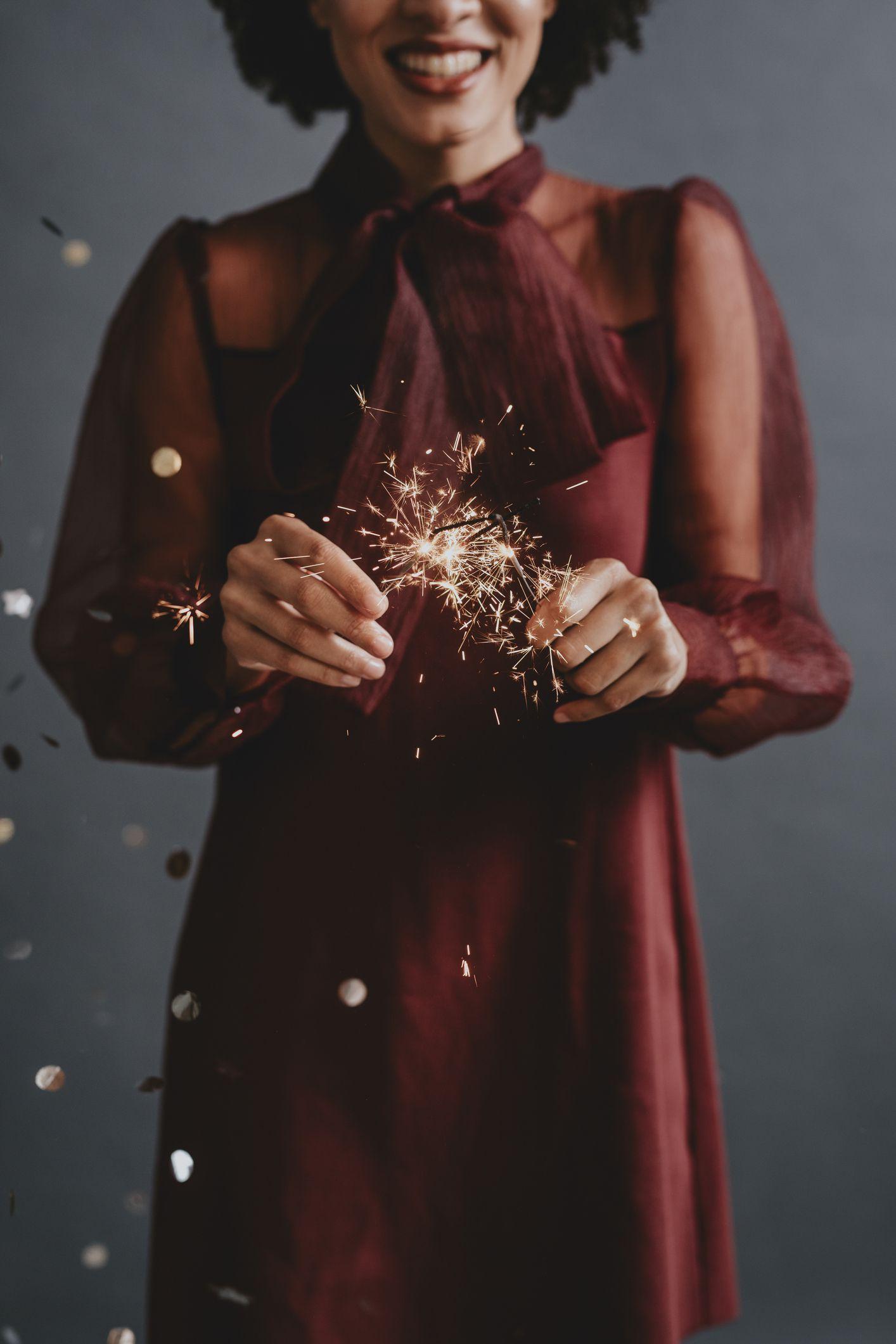 portret anonimne nasmiješene žene u svečanoj crvenoj haljini koja drži blistave, koncept proslave
