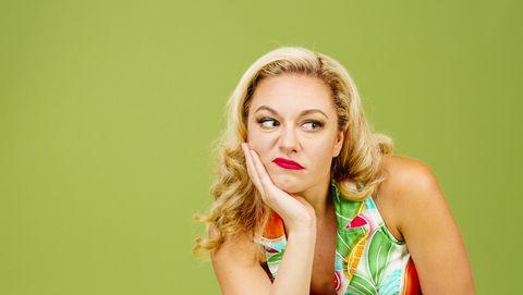 jaloerse vrouw met blond haar op groene achtergrond