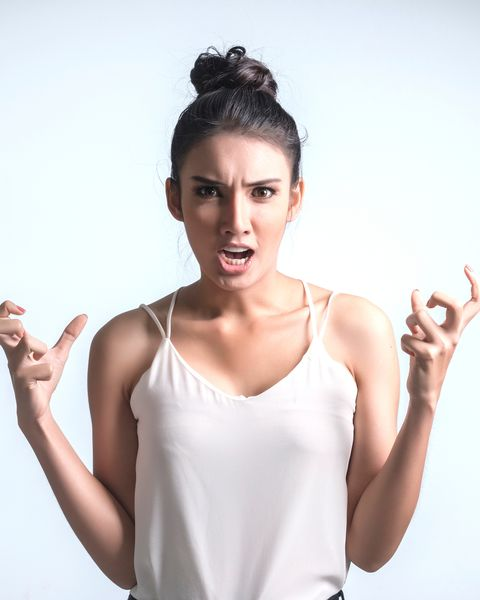 Portrait Of Angry Young Woman Standing Against White Background