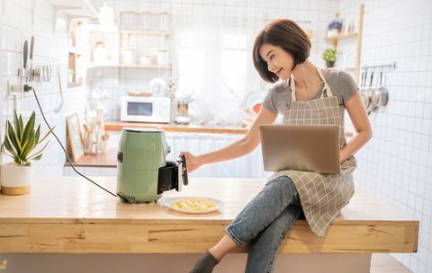 portrait of asian girl cooking potato fried by air fryer machine in kitchen home new normal work at home lifestyle technology eco friendly home smart device concept