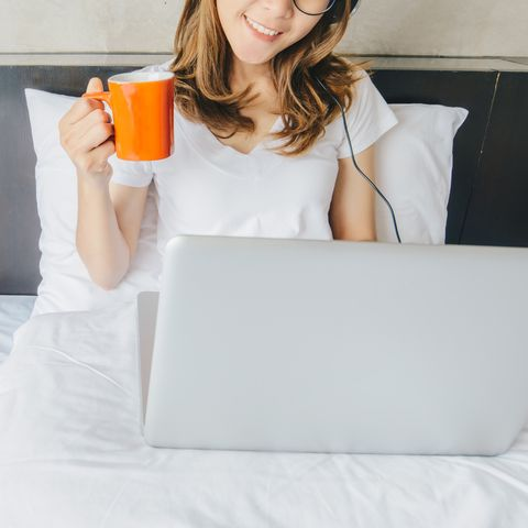 portrait of asian woman enjoying her holiday by using computer laptop and listening music with a cup of coffee on her bed