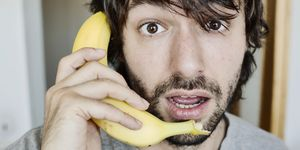 Portrait of astonished young man telephoning with banana