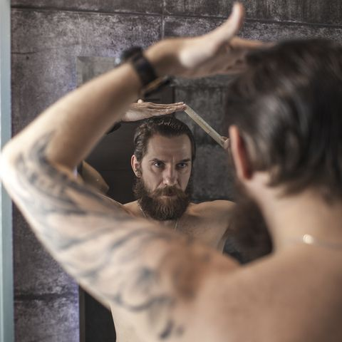 portrait of bearded man looking at his mirror image while combing his hair