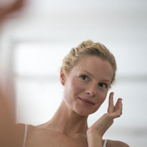 portrait of beautiful blond woman applying eye cream