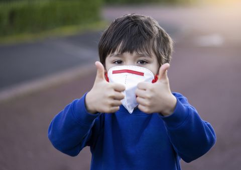 portrait of boy wearing mask gesturing outdoors