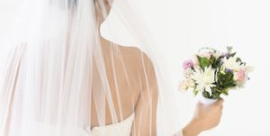 Portrait of bride in veil holding bouquet