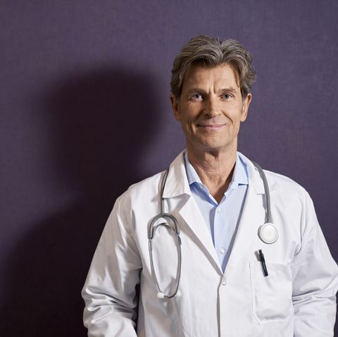 portrait of confident doctor in front of a purple wall