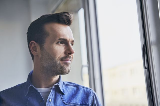 portrait of confident man looking out of window