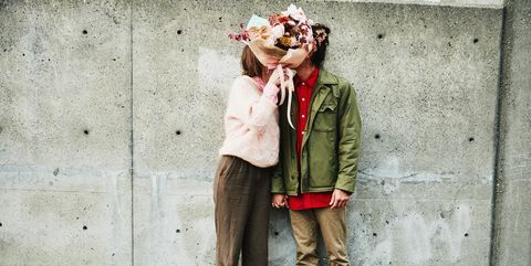 Portrait of couple kissing while hidden behind bouquet of flowers