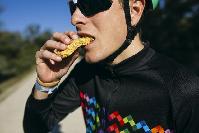 portrait of cyclist eating a snack during a break on a sunny day
