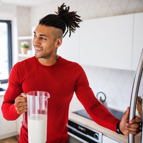 a portrait of fit mixed race man getting milk from fridge after doing exercise at home