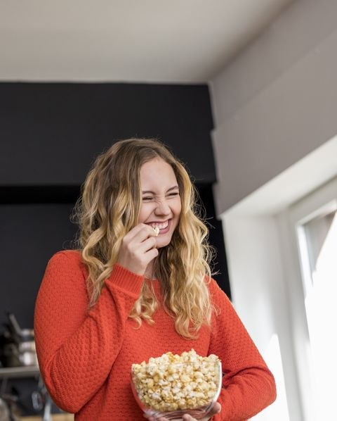 Portrait of giggling young woman with bowl of popcorn in the kitchen