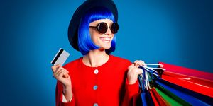 Portrait of glad woman in red outfit showing gesturing plastic credit card for comfortable quickly shopping in internet holding colorful packets in hand looking away isolated on blue background