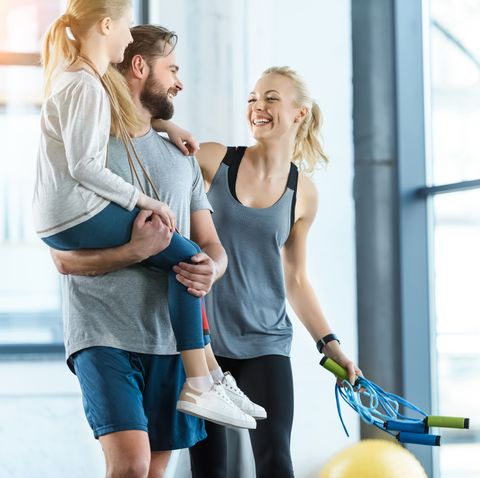 Portrait of happy family standing together at fitness center