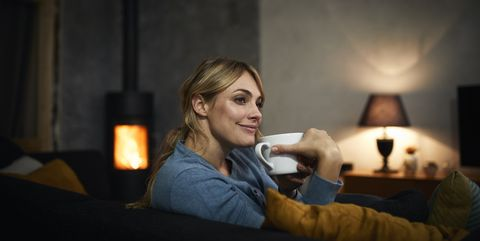 Portrait of happy woman with cup of tea relaxing on couch at home in the evening