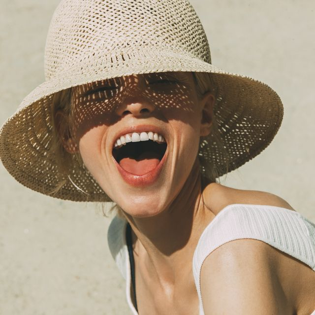 Portrait of laughing blond woman wearing summer hat