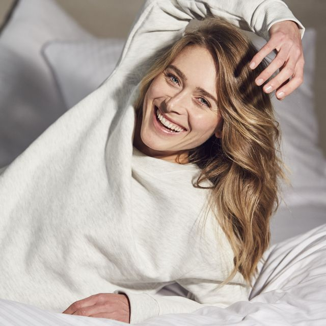 Portrait of laughing woman lying on bed