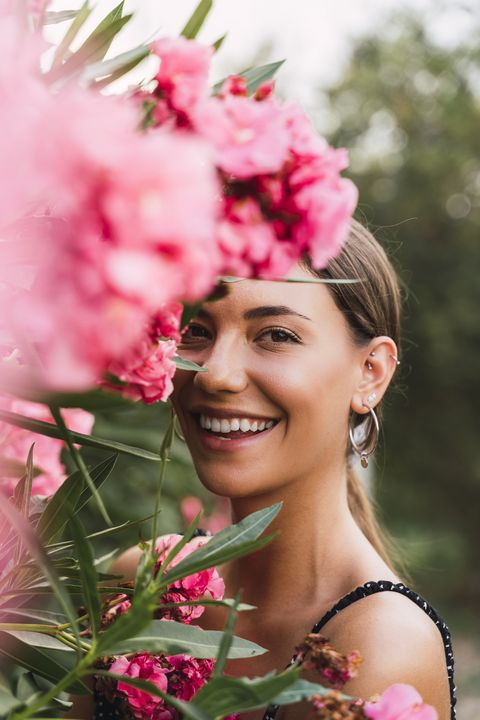 portrait of laughing young woman in a park with pink blossoming flowers