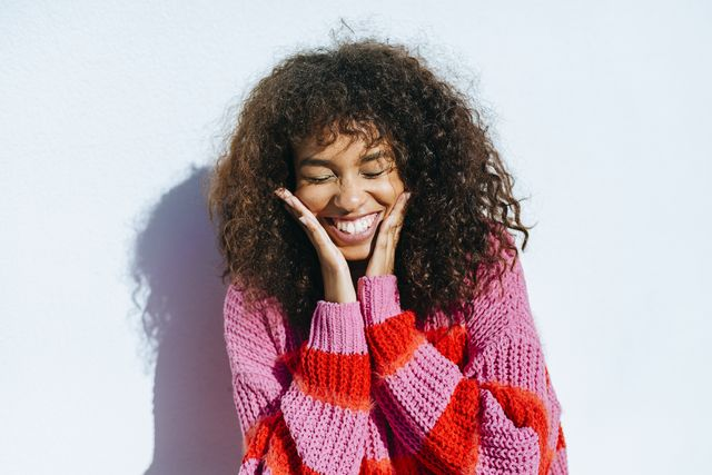 portrait of laughing young woman with curly hair against white wall