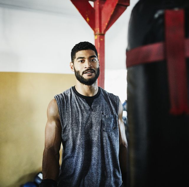 portrait of male boxer standing by heavy bag in boxing gym
