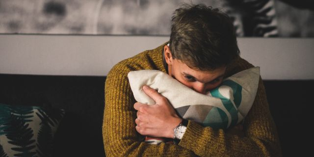 portrait of man hugging a pillow at home