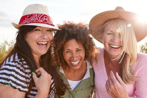portrait of mature female friends walking through field on camping vacation