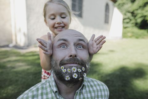 portrait of mature man with daisies in his beard playing with little daughter in the garden