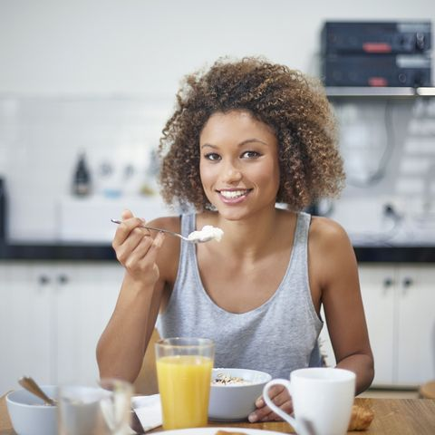 portrait of mixed race young woman having breakfast at kitchen