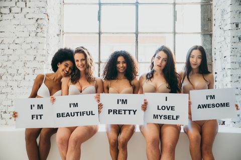 portrait of multi ethnic women in lingerie holding messages while sitting on retaining wall